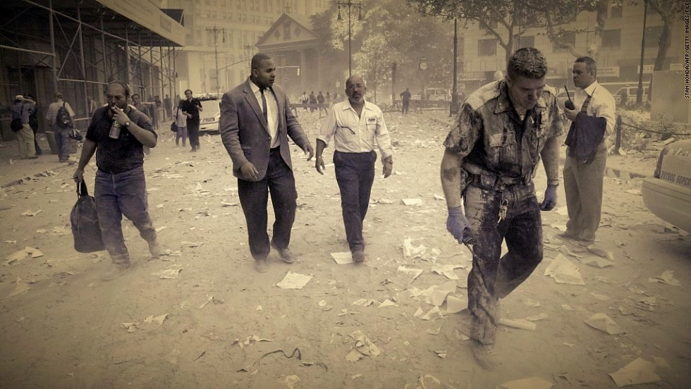 (FILES) A police officer (R) and others walk in the streets covered in debris near the World Trade Center towers after two planes hijacked by terrorists flew into the two towers in New York, on September 11, 2001. US President Barack Obama said on May 1, 2011 that justice had been done after the September 11, 2001 attacks with the death of Osama bin Laden, but warned that Al-Qaeda will still try to attack the US.        AFP PHOTO/Stan HONDA (Photo credit should read STAN HONDA/AFP/Getty Images)